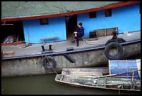 Man sitting on a house boat. Leshan, Sichuan, China