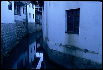 White walled houses surrounding a canal. Lijiang, Yunnan, China