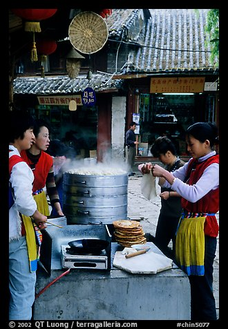 Naxi women selling dumplings and Naxi baba flatbread. Lijiang, Yunnan, China