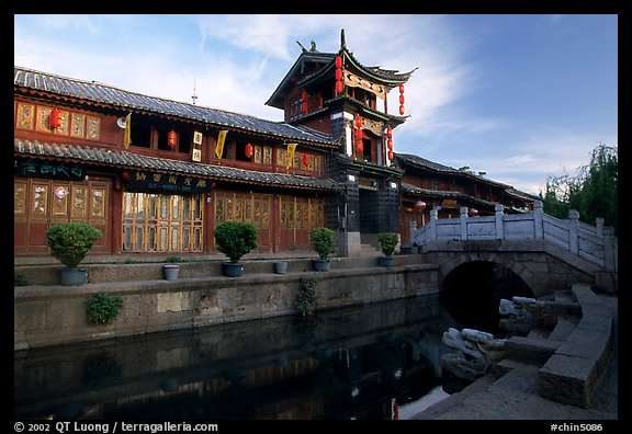 Kegong tower (memorial archway of imperial exam) reflected in canal, sunrise. Lijiang, Yunnan, China