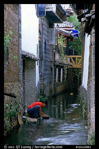 Woman washes clothes in the canal. Lijiang, Yunnan, China (color)