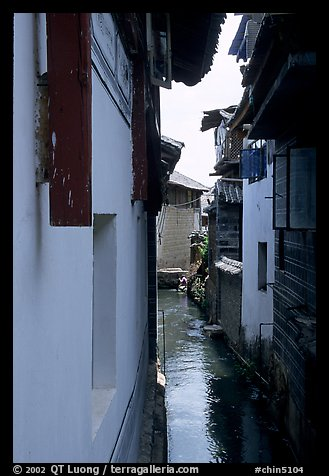 Canal sneaking narrowly between walls. Lijiang, Yunnan, China (color)