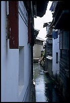 Canal sneaking narrowly between walls. Lijiang, Yunnan, China ( color)
