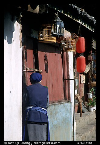 Naxi woman at the door of her wooden house. Lijiang, Yunnan, China