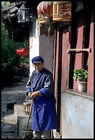 Naxi woman at the door of her wooden house. Lijiang, Yunnan, China ( color)