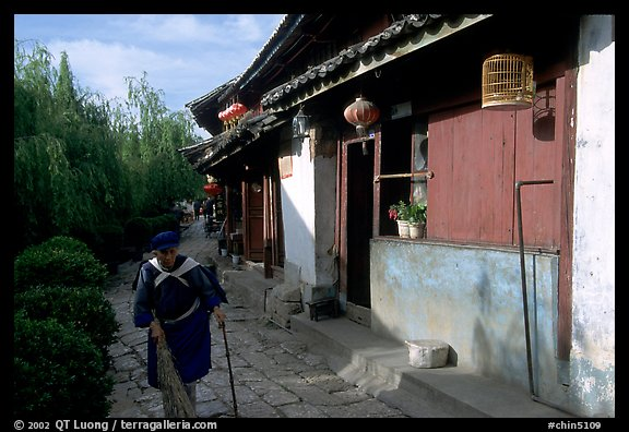 Naxi woman sweeps the floor at the door of her wooden house. Lijiang, Yunnan, China