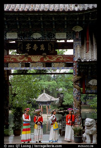 Women in Naxi dress standing in an archway. Lijiang, Yunnan, China