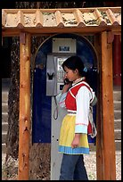Woman in Naxi dress in a telephone booth. Lijiang, Yunnan, China (color)