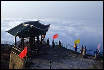 Monks and pilgrims admiring a sea of cloud from the summit. Emei Shan, Sichuan, China