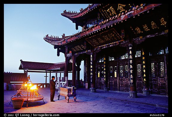 Pilgrim prays in the Jinding Si (Golden Summit) temple at dusk. Emei Shan, Sichuan, China (color)