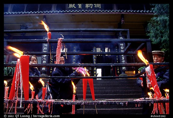 Pilgrims lighting incense sticks with Wannian Si temple in the background. Emei Shan, Sichuan, China (color)