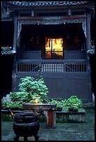 Buddha image seen from rainy courtyard of Hongchunping temple. Emei Shan, Sichuan, China (color)