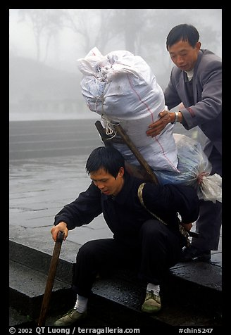 Porter getting helped to shoulder a heavy load on a back frame. Emei Shan, Sichuan, China (color)