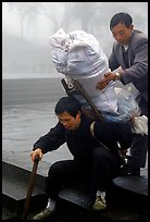 Porter getting helped to shoulder a heavy load on a back frame. Emei Shan, Sichuan, China ( color)