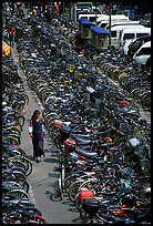 Woman walking in a bicycle parking lot. Chengdu, Sichuan, China