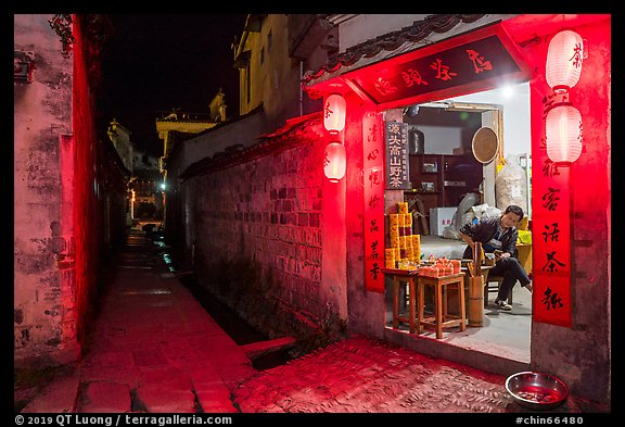Shopkeeper and alley at night. Hongcun Village, Anhui, China (color)