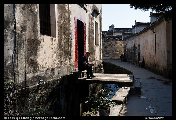 Man sitting in front of house on bridge over stream. Xidi Village, Anhui, China (color)