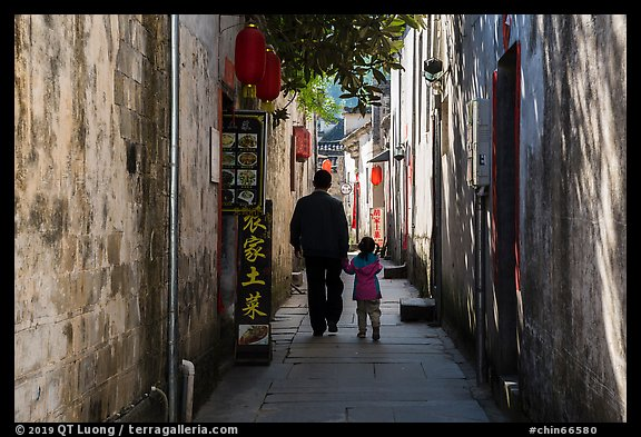 Father and daughter walking in alley. Xidi Village, Anhui, China (color)