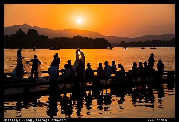 Couple embracing at sunset among crowd, West Lake. Hangzhou, China (color)