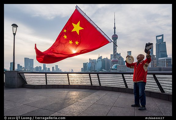 Man saluting Chinese flag and skyline, the Bund. Shanghai, China (color)