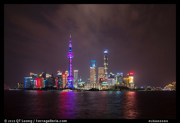 Shanghai skyline with Oriental Perl Tower and Huangpu River at night. Shanghai, China (color)