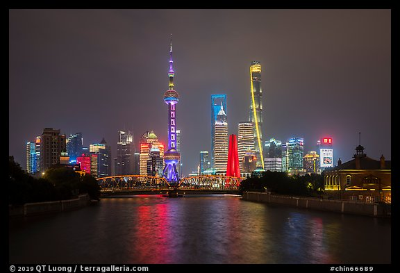 Garden Bridge, Peoples Memorial and city skyline at night. Shanghai, China (color)