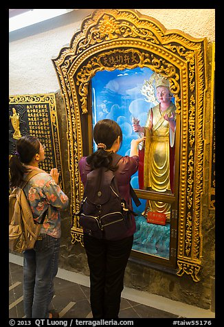 Women pray to deity, Guandu Temple. Taipei, Taiwan (color)