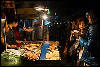 Sampling snacks at Shilin Night Market. Taipei, Taiwan (color)