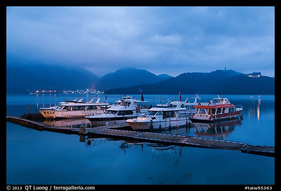 Pier with distant lights of Itashao Village and Syuanzang Temple at dawn. Sun Moon Lake, Taiwan (color)