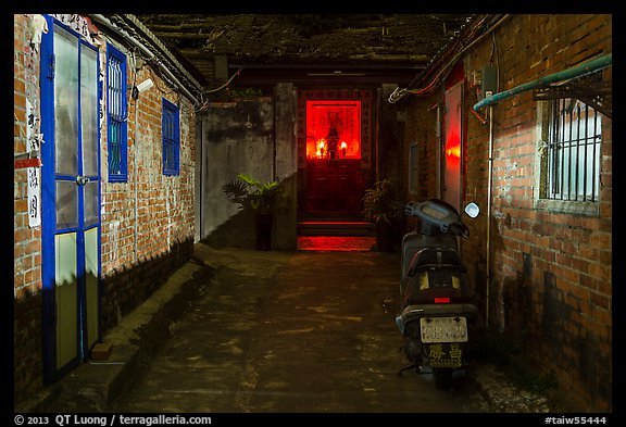 Alley at night with temple altar glowing red. Lukang, Taiwan (color)