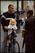 Blond little girl sitting on bicycle. Bruges, Belgium (color)