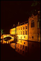 Houses and bridge reflected in canal at night. Bruges, Belgium