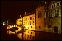 Bridge and houses reflected in canal at night. Bruges, Belgium