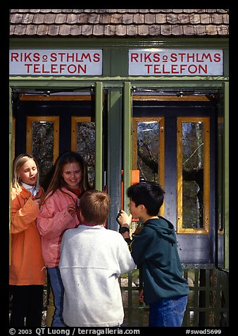 Swedish kids in a phone booth. Stockholm, Sweden (color)