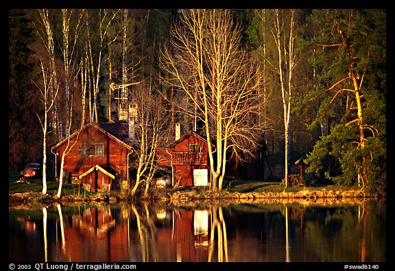 Wooden house reflected in a lake at sunset. Central Sweden (color)
