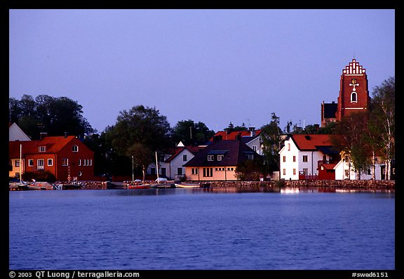 Houses, church, across the lake at dusk, Vadstena. Gotaland, Sweden (color)
