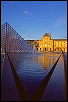 Pyramid and triangular basin in the Louvre, sunset. Paris, France