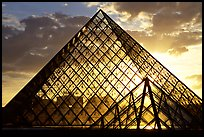 Sunset and clouds seen through Pyramid, the Louvre. Paris, France