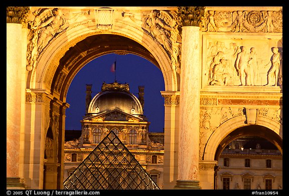 Louvre and  pyramid  seen through the Carousel triumphal arch at night. Paris, France (color)