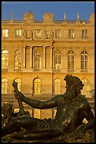 Statue, basin, and Versailles palace facade, late afternoon. France