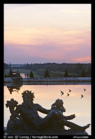 Sculptures, basin, and gardens at dusk, Versailles Palace. France (color)