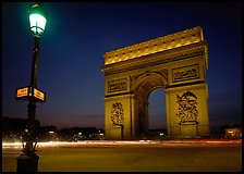 Street lamp and Etoile triumphal arch at night. Paris, France (color)