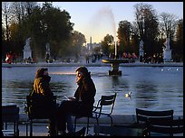 Couple sitting by basin in Tuileries Gardens. Paris, France (color)