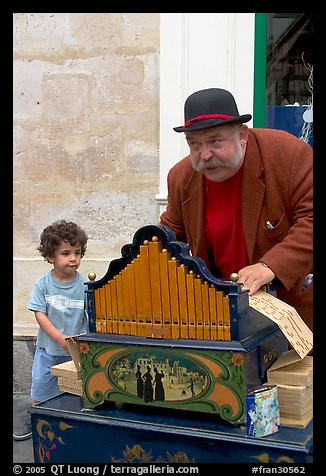 Barrel organ player and kid. Quartier Latin, Paris, France (color)