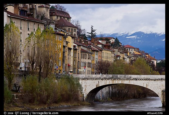 Stone bridge, houses, and snowy mountains. Grenoble, France