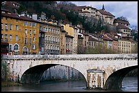 Stone bridge and brightly painted riverside townhouses. Grenoble, France