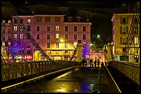 Pedestrians on suspension bridge at night. Grenoble, France (color)