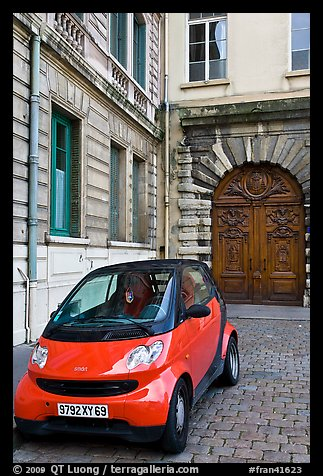 Tiny car on coblestone pavement in front of historic house. Lyon, France (color)