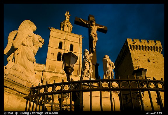 Cross with Christ, statues, and towers, evening light. Avignon, Provence, France (color)