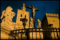Cross with Christ, statues, and towers, evening light. Avignon, Provence, France ( color)